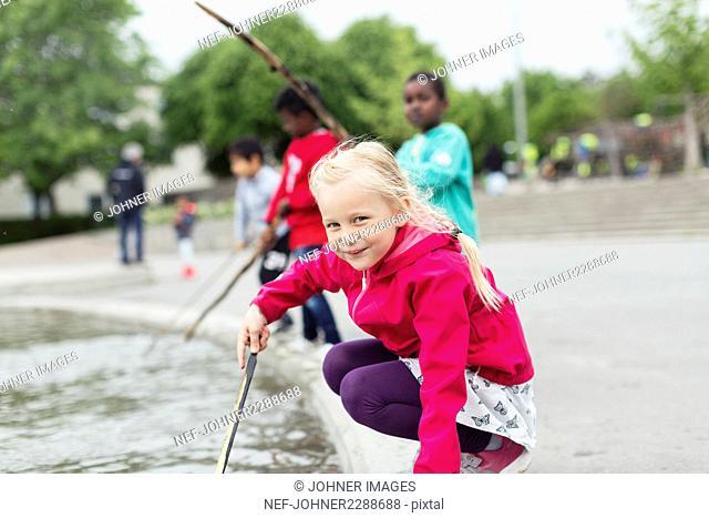 Girl playing at pond