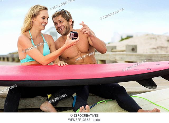 Happy couple with surfboard and camera talking on the beach