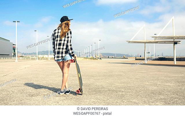 Back view of young woman with longboard standing in front of beach promenade, partial view