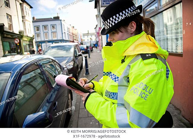 A woman Dyfed-Powys police officer issuing parking ticket to a car parked on double yellow lines, Aberystwyth Wales UK