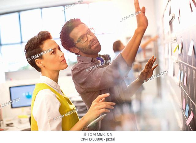 Creative business people planning, scheduling at calendar blackboard