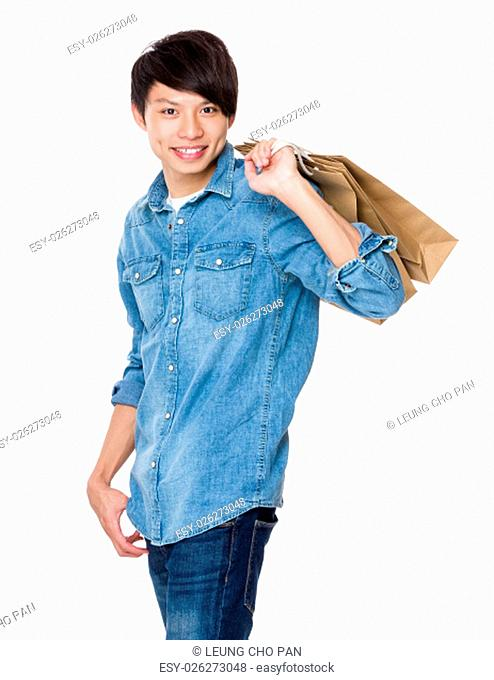 Asian man holding up with paper bag