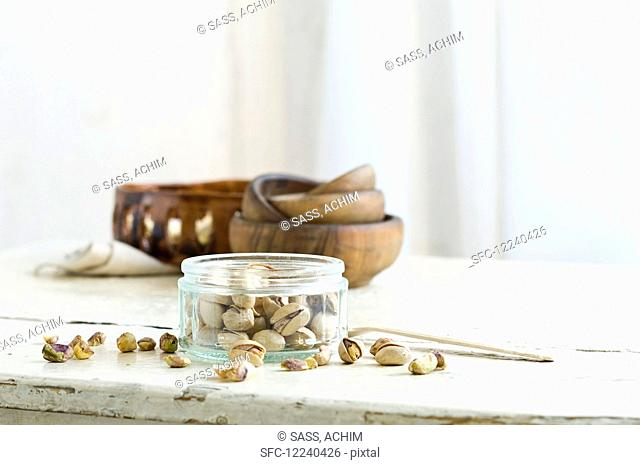 Pistachios in and next to a glass jar on a rustic kitchen table