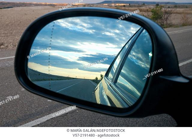Side road viewed on a rear mirror at nightfall