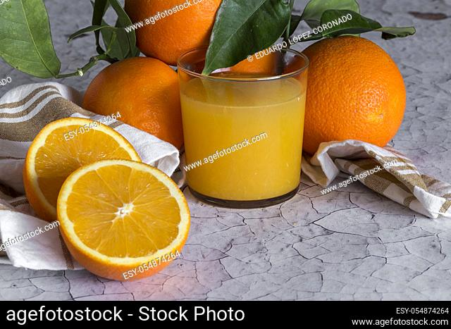 Fresh natural oranges juice in glass cup. On wooden table