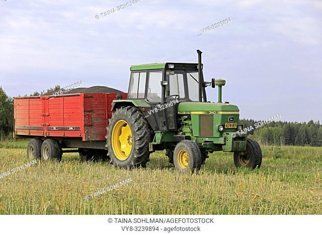 Salo, Finland - September 8, 2018: John Deere 3140 farm tractor and agricultural trailer full of harvested rapeseed on a beautiful day of autumn