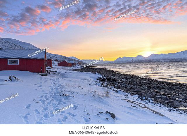 Sunset among the fishermen's houses overlooking the fjord. Nordmannvik, Kafjord, Lyngen Alps, Troms, Norway, Lapland, Europe