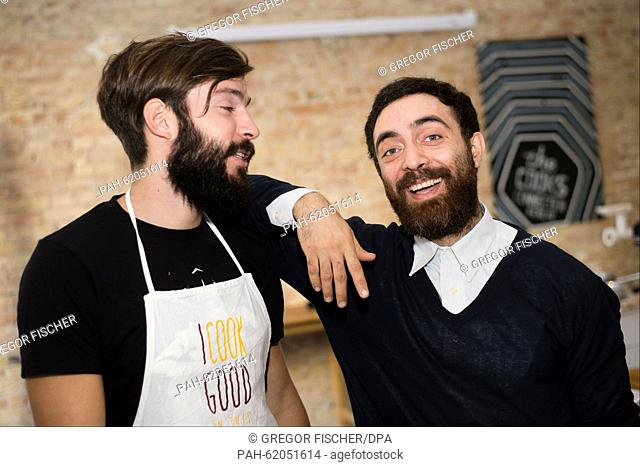 Syrian refugee Mudar Alscheich (r) and his colleague Gerrit Kuerschner smile during an interview in a communal kitchen in Berlin, Germany, 24 September 2015