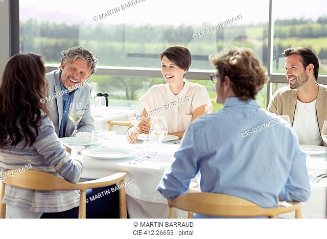 Friends drinking white wine and talking at sunny restaurant table