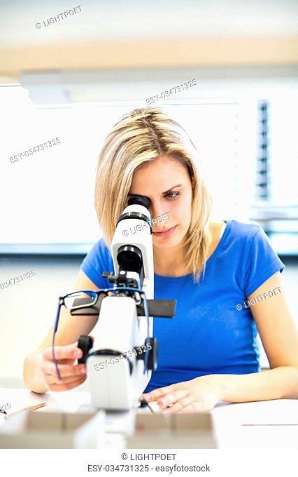 Pretty, young female optician/optometrist measuring new glasses she has prepared for a customer