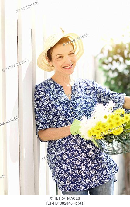Portrait of smiling senior woman with flowers