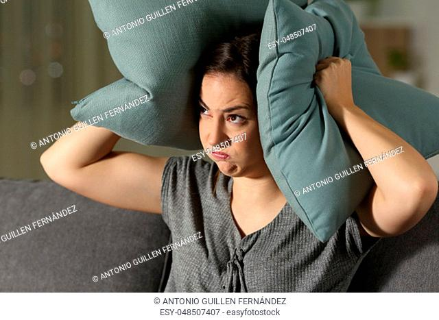 Angry woman suffering neighbour noise sitting on a couch in the living room at home