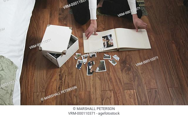 woman tearing up photos in her bedroom