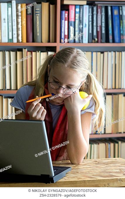 Girl with a computer in the reading room