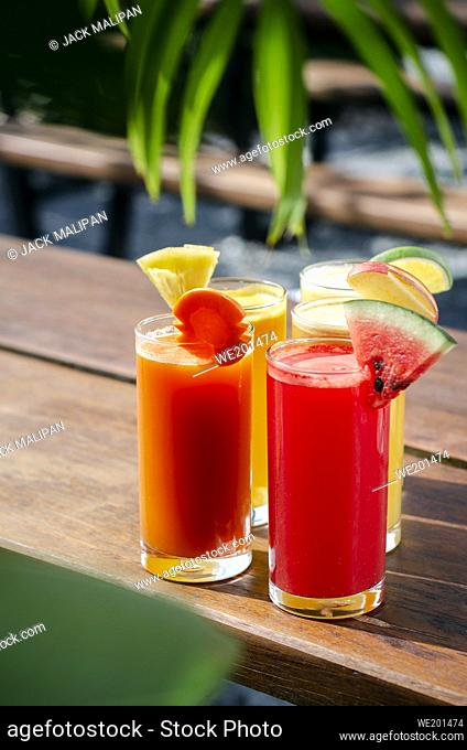 mixed fresh organic fruit juice glasses selection on sunny garden table