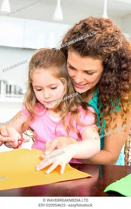 Little girl making paper shapes with mother at the table