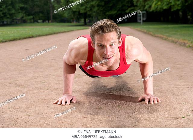 Man in sports clothes, push-ups, looking at camera