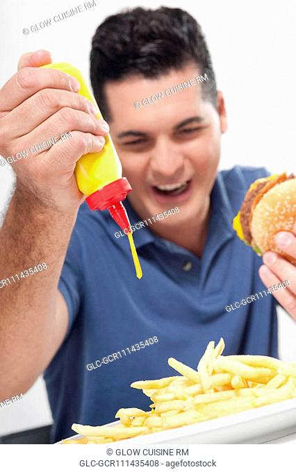Man squeezing mustard on fries