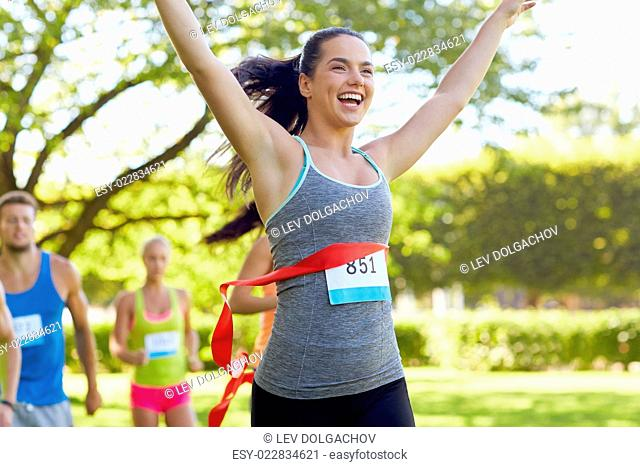 fitness, sport, victory, success and healthy lifestyle concept - happy woman winning race and coming first to finish red ribbon over group of sportsmen running...
