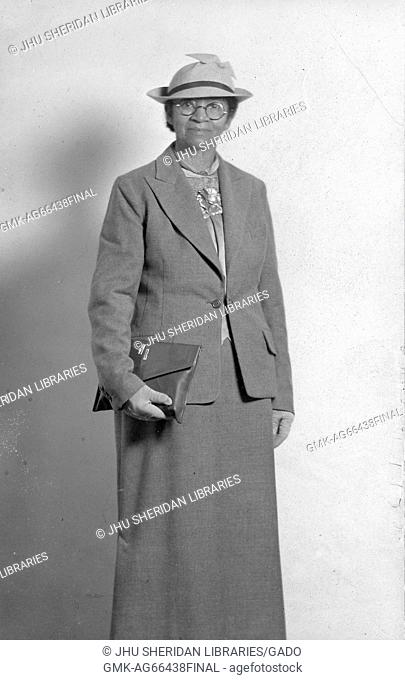 Three quarter length standing portrait of elderly African American woman, wearing dark skirt, blouse, jacket, gloves, glasses and hat, carrying clutch