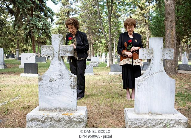 Two Women Holding Single Red Roses Standing At Two Graves Side By Side In A Cemetery; Edmonton, Alberta, Canada