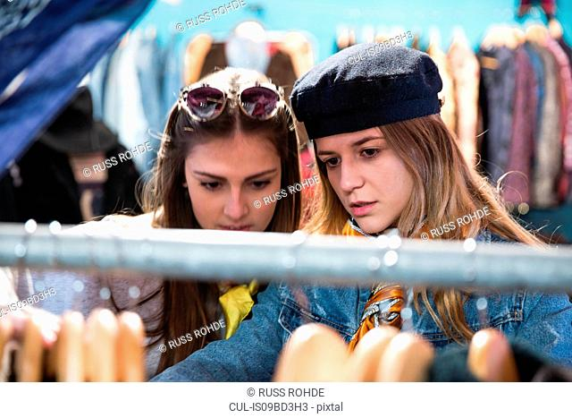 Friends browsing vintage clothes in thrift store