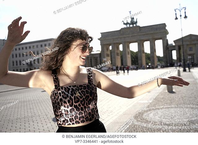 lively young woman dancing in front of Brandenburg Gate, Brandenburger Tor, in Berlin, Germany
