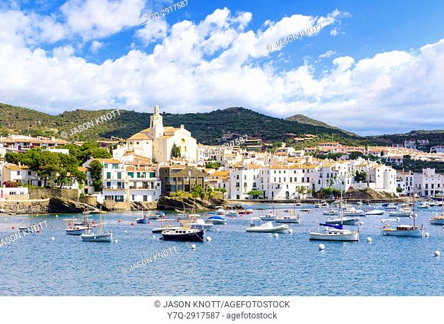 Whitewashed Cadaqués Town, topped by the Church of Santa Maria overlooking boats in the blue waters of Cadaqués Bay, Catalonia, Spain