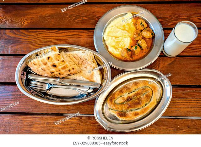 Burek with bread, potato and meat balls in metal plates on wooden table. Traditional balkan's food