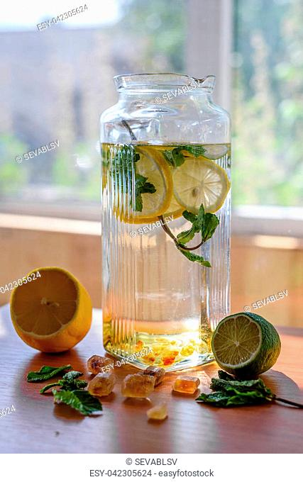 Summer homemade lemonade in pitcher with lime and lemon on window background. Sweet and sour refreshing taste