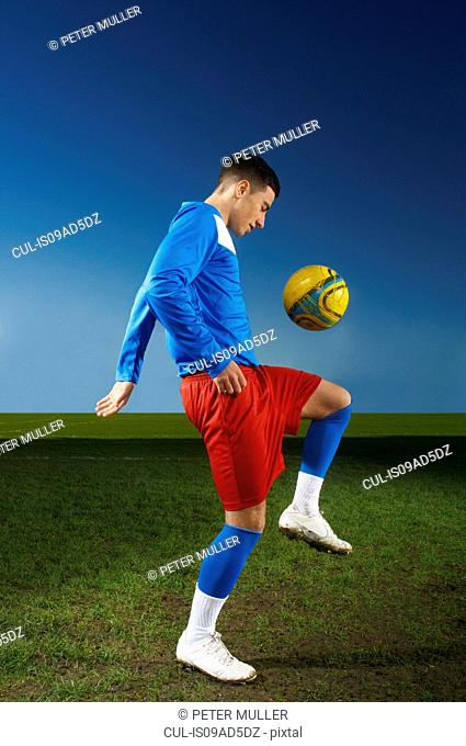 Young man playing keepy uppy with football