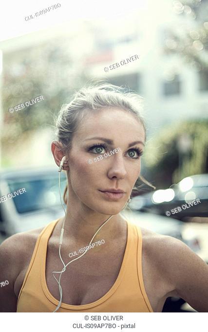 Portrait of young woman wearing earphones