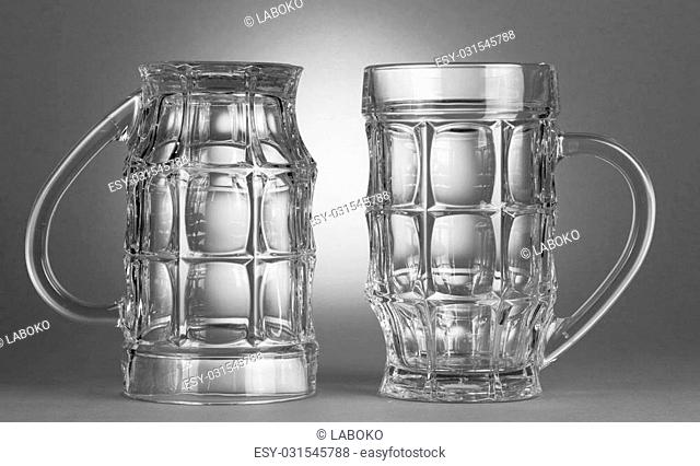 Two empty beer glasses on grey background
