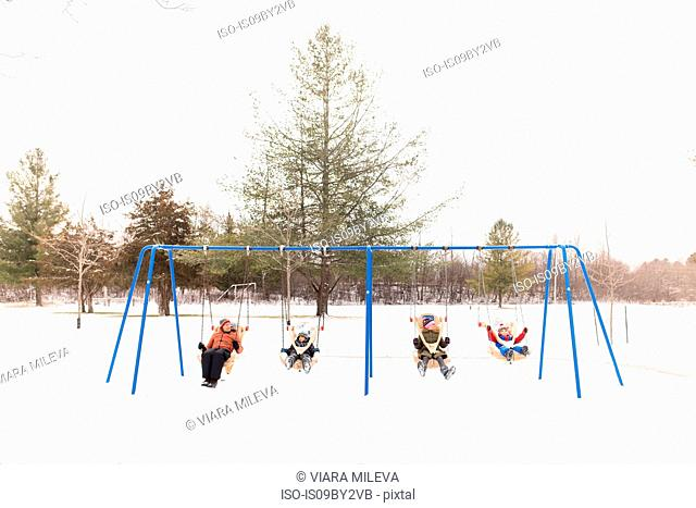 Man and children swinging on row of playground swings in snow