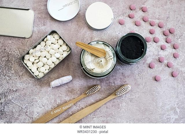 High angle close up of wooden toothbrushes, homemade cosmetics and pills in metal box