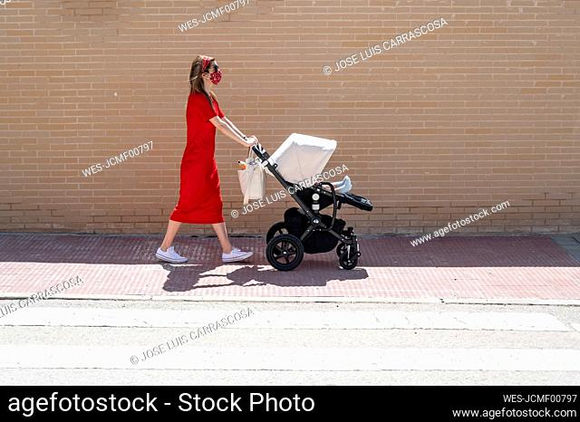 Mother wearing mask pushing son in baby carriage while walking on sidewalk