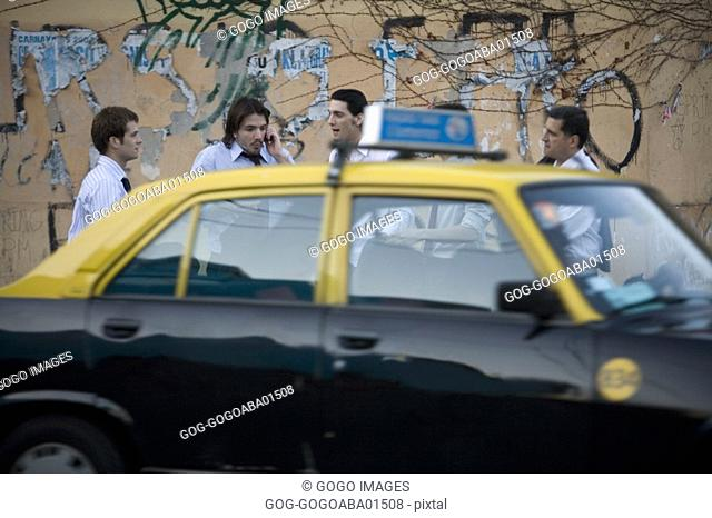 Taxi driving past group of businessmen