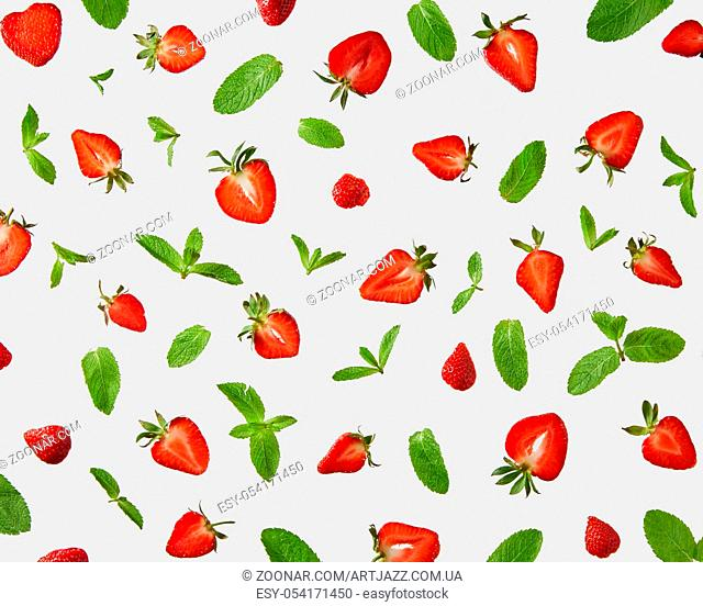 Pattern of fresh halves of ripe strawberries and green mint leaves on a gray background, flat lay