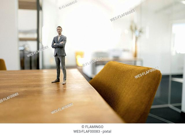 Businessman figurine standing on desk in modern office