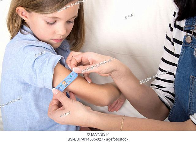 Mother putting a bandaid on her daughter's arm