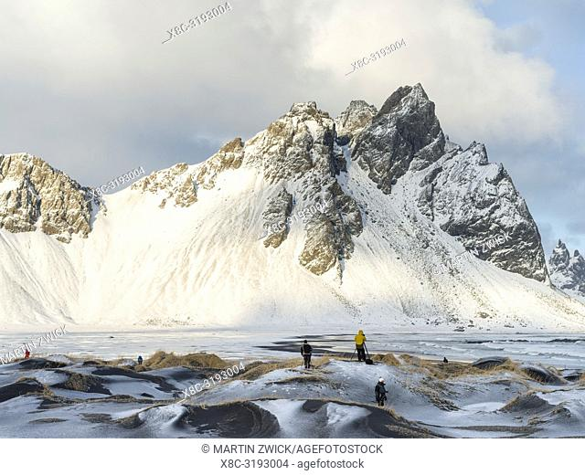 Tourists in coastal landscape with dunes at iconic Stokksnes during winter and stormy conditions. europe, northern europe, iceland, february