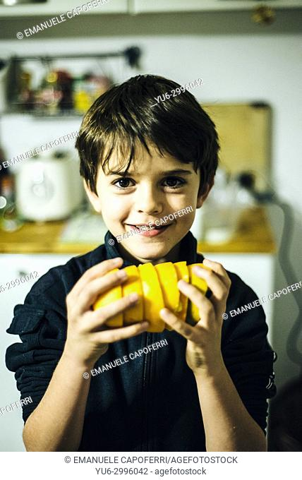 Boy plays with orange peels