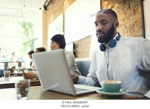 Young man with headphones using laptop and drinking coffee in cafe