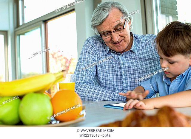 Grandfather and grandson using tablet