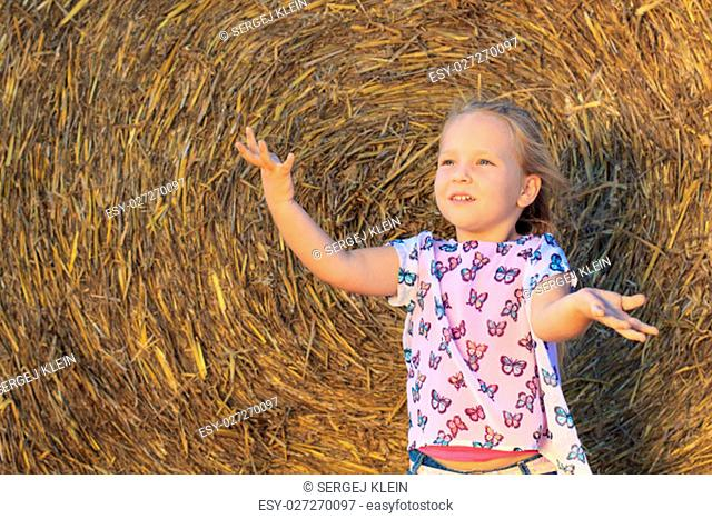 A little girl having fun with hay on a farm. Happy childhood, lifestyle concept