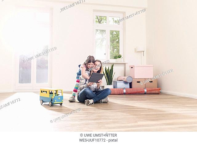 Happy girl and mother with tablet in empty apartment
