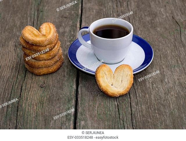 pile of cookies and cup of coffee on a wooden table, a still life on a subject drinks and sweets