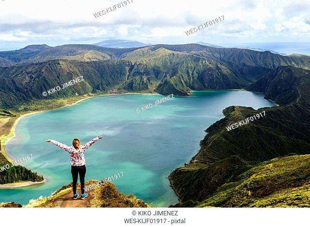 Azores, Sao Miguel, Woman with raised arms on the top of the Lagoa do Fogo