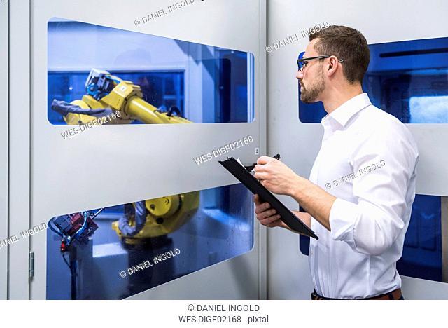 Man taking notes at robotics machine in factory shop floor