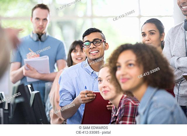 College students listening and taking notes in classroom
